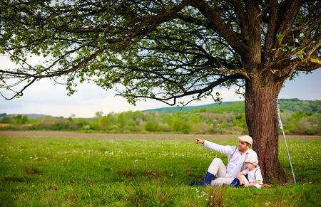 папа: Фермер отец и сын, сидя под деревом весеннего сельской местности