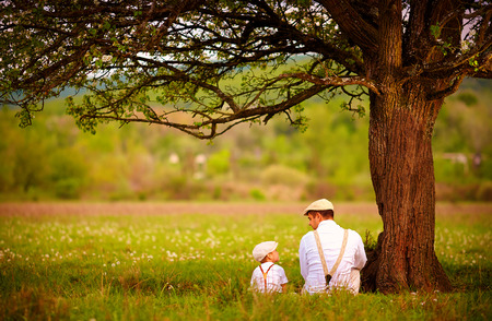 familias felices: padre e hijo sentados bajo el árbol en el jardín de primavera