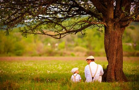 Vater und Sohn sitzen unter dem Baum auf Frühlingswiese Standard-Bild
