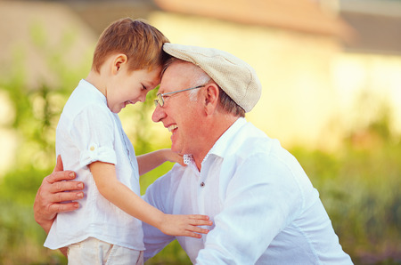 grandfather and grandson: portrait of happy grandfather and grandson bow their heads