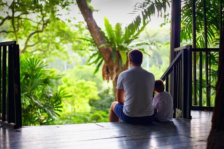 famiglia in giardino: padre e figlio seduti sulle scale di casa albero nella foresta tropicale