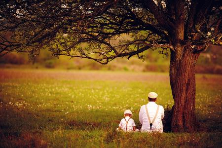 Padre e hijo se sienta bajo el árbol en el jardín de primavera