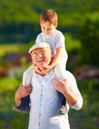 happy grandson sitting on shoulders of grandpa countryside