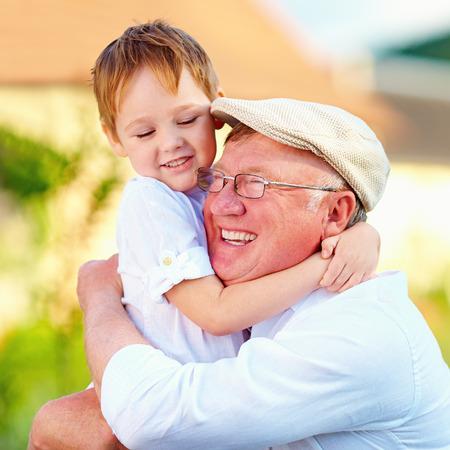 Portret van gelukkige opa en kleinzoon in openlucht omhelst