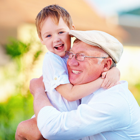 love hug: portrait of happy grandpa and grandson having fun outdoors Stock Photo