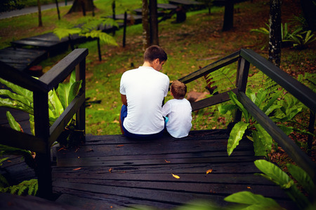 father and son sitting on wooden stairs in rain forest