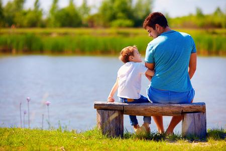 gelukkige vader en zoon zitten op de oever van de rivier Stockfoto