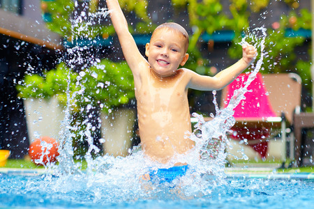 pool water: excited happy kid boy jumping in pool, water fun Stock Photo
