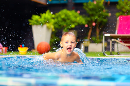 kids jumping: excited happy kid boy jumping in pool, water fun Stock Photo
