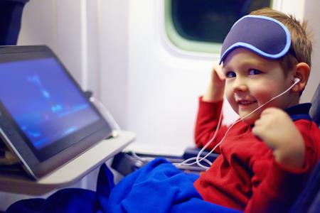 caricatura mosca: lindo niño pequeño viendo dibujos animados durante el largo vuelo en avión Foto de archivo