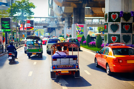 main street: traditional vehicles moving on the main road in Bangkok, Thailand Stock Photo