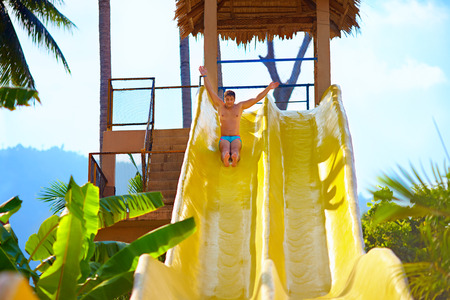 recreate: excited man having fun on water slide in tropical aqua park