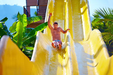 aqua: excited man having fun on water slide in tropical aqua park