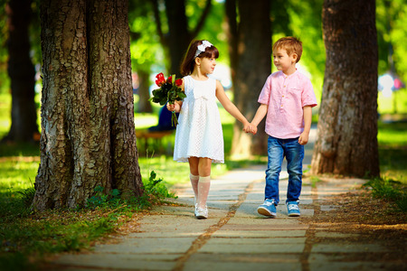 cute kid walking together in summer park Stock Photo
