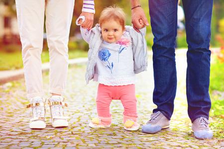 niña linda bebé en pie con los padres, primeros pasos