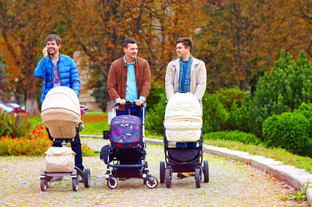 single family: three happy fathers on city walk in park