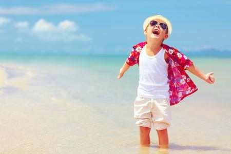 幸せなファッショナブルな子供少年夏のビーチでの生活を楽しんでいます