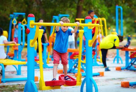 niños en area de juegos: chico lindo, muchacho ejercicio en terreno del deporte con otras personas en el fondo Foto de archivo