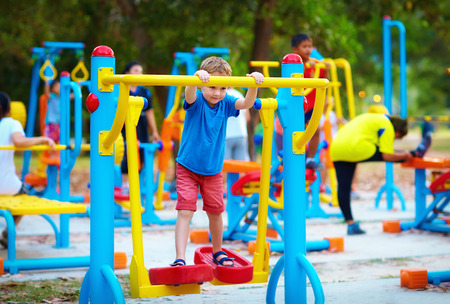 area: cute kid, boy exercising on sport ground with other people on background