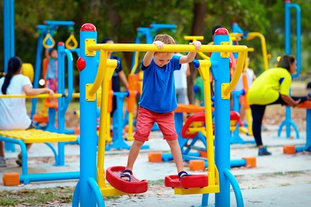 a place of life: cute kid boy exercising on sport ground with other people on background