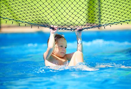 stunt: cute boy kid having fun, making stunt on volleyball net in pool