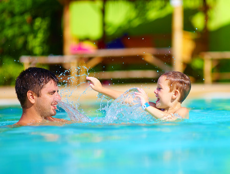 dabbling: happy father and son dabbling in pool water, summer holiday
