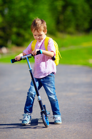 cute kid boy riding a scooter on the road summer outdoors Stock Photo