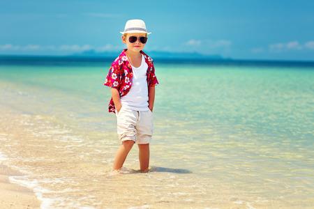 mode: schattige modieuze jongen staat in de branding op de zomer strand Stockfoto
