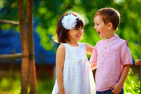 gemelos niÑo y niÑa: niños riendo lindos que se divierten al aire libre, el verano Foto de archivo