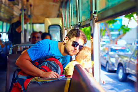 pass on: father and son traveling in public bus without windows through asian city