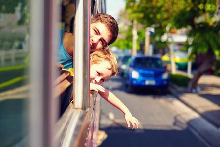 passenger buses: padre e hijo viajar en autobús público y sin ventanas, a través de la ciudad asiática