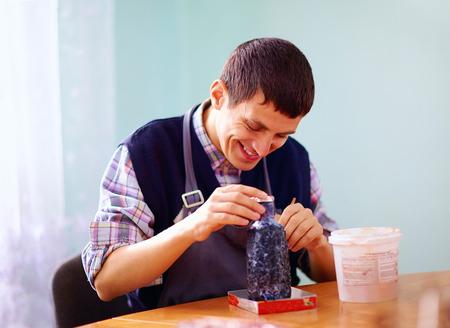 jong volwassen man met een handicap die zich bezighouden met vakmanschap op praktische les, in revalidatiecentrum