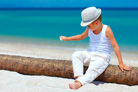 cute young boy: cute fashionable kid, boy playing with shell on tropical beach