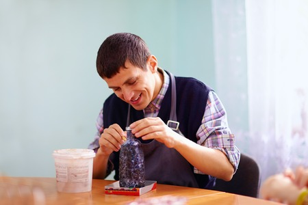 needs: young adult man with disability engaged in craftsmanship on practical lesson, in rehabilitation center
