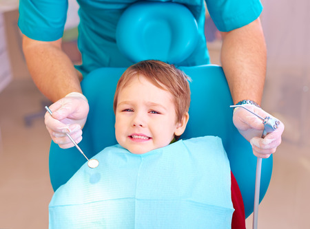 little kid patient afraid of dentist while visiting dental clinic Archivio Fotografico