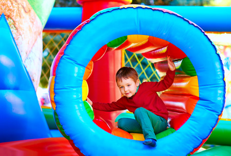 leisure activities: cute happy kid boy playing in inflatable attraction on playground