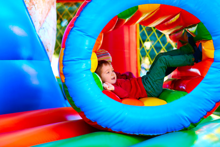 daycare: cute happy kid boy playing in inflatable attraction on playground