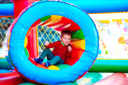 cute happy kid boy playing in inflatable attraction on playground