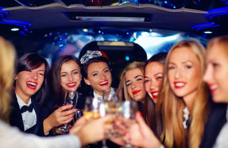 group of happy elegant women clinking glasses in limousine hen party
