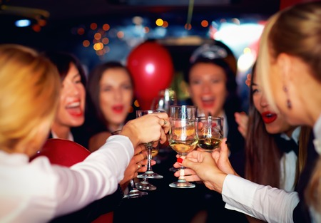 happy elegant women clinking glasses in limousine focus on glasses