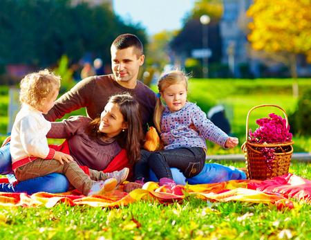 embrace family: familia feliz en comida campestre del otoño en el parque Foto de archivo
