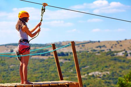 若い女性が山の極端なスポーツのジップライン降下する準備ができています。 写真素材 - 41117956
