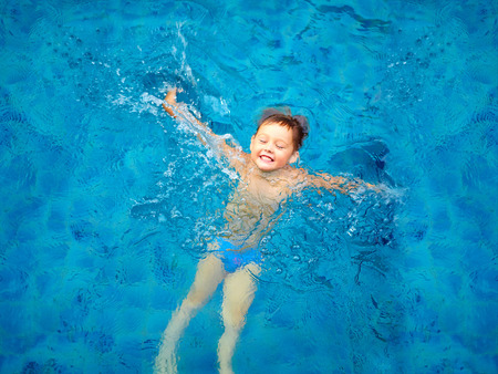 cute kid boy swimming in pool water top view
