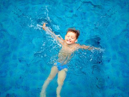 schattig kind jongen zwemmen in het zwembad water bovenaanzicht Stockfoto