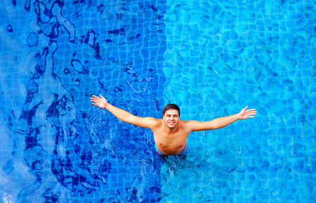 rise to the top: happy man enjoying vacation while standing in pool water top view