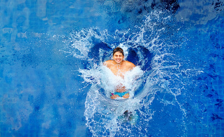 pool fun: man jumping in pool huge splash top view