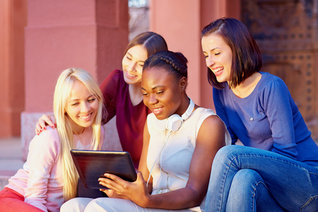 watch video: beautiful multiracial female friends socializing through the internet on tablet