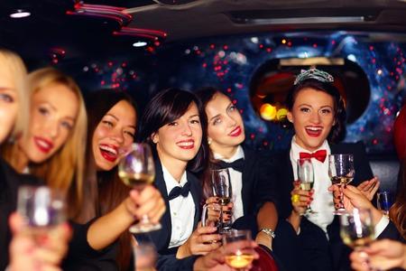 vestido de noche: grupo de mujeres elegantes felices que tintinean los vidrios en despedida de soltera de limusina
