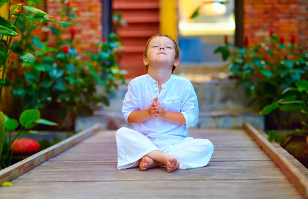 cute boy trying to find inner balance in meditation Stockfoto