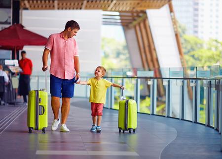 gente aeropuerto: feliz padre e hijo están listos para el embarque en el aeropuerto internacional